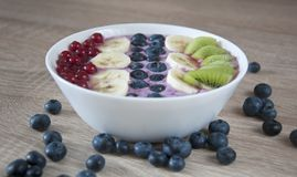 Healthy oatmeal with fruits and yoghurt. Tasty and healthy breakfast. Fresh oatmeal with blueberry yoghurt, bananas, kiwi and currants. Closeup photo royalty free stock photography