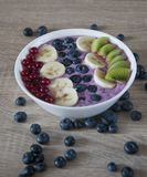 Healthy oatmeal with fruits and yoghurt. Tasty and healthy breakfast. Fresh oatmeal with blueberry yoghurt, bananas, kiwi and currants. Closeup photo stock image