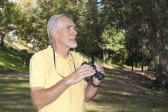 Healthy old man using binoculars to birdwatch