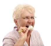 Healthy old woman eating garlic Royalty Free Stock Image