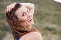 Healthy older woman smiling outside with hand in hair Royalty Free Stock Photo
