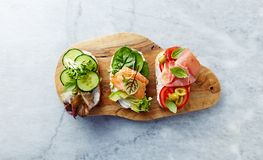Healthy open sandwiches with vegetables, herbs, salmon, ham, herbs and soft cheese. Healthy diet concept. Healthy open sandwiches with vegetables, herbs, salmon stock photography
