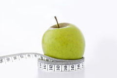 Healthy Options. Macro shot of a ripe green apple and  glass of orange juice with a waist line tape measure around the apple The shot depicts a slimmer waistline Stock Photo