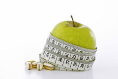 Healthy Options. Macro shot of a ripe green apple and  glass of orange juice with a waist line tape measure around the apple The shot depicts a slimmer waistline Stock Photography