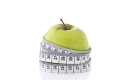 Healthy Options. Macro shot of a ripe green apple and  glass of orange juice with a waist line tape measure around the apple The shot depicts a slimmer waistline Royalty Free Stock Photo