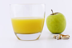 Healthy Options. Macro shot of a ripe green apple and  glass of orange juice with a waist line tape measure around the apple The shot depicts a slimmer waistline Stock Photos