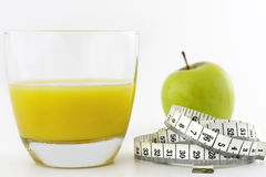Healthy Options. Macro shot of a ripe green apple and  glass of orange juice with a waist line tape measure around the apple The shot depicts a slimmer waistline Royalty Free Stock Image