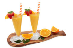 Healthy Orange Juice Drink. Orange fruit juice drink in glasses with fresh strawberries, striped straws on an olive wood board over white background. High in royalty free stock photography