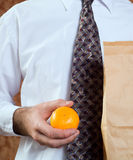 Healthy Orange Snack. Closeup of a businessman holding his paper bagged lunch and an orange Stock Photos