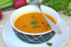 Healthy orange soup from pumpkin hokaido, green celery, garlic, onion and parsley in boxl with spoon on brown cloth and wooden bac Royalty Free Stock Images