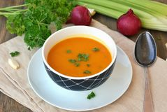 Healthy orange soup from pumpkin hokaido, green celery, garlic, onion and parsley in boxl with spoon on brown cloth and wooden bac Stock Photos