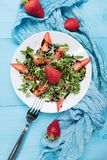 Healthy organic diet salad with arugula, strawberries and sesame with balsamic glaze in white plateon a pastel blue wooden stock photos