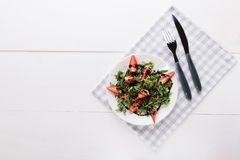 Healthy organic diet salad with arugula, strawberries and sesame in white plate on grey napkin on a white wooden background with stock images