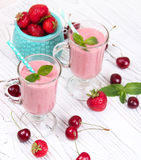 Healthy organic food. Strawberry fruit drink smoothie. Healthy berry cocktail with scattered berries of cherries and strawberries on the rustic background of a Royalty Free Stock Photo