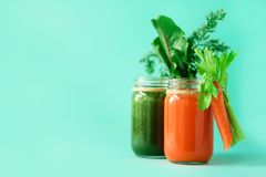 Healthy organic green and orange smoothies on blue background. Detox drinks in glass jar from vegetables - carrot. Celery, beet greens and tops. Copy space stock image