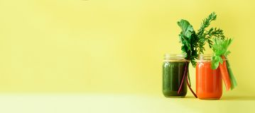 Healthy organic green and orange smoothies on yellow background. Banner. Detox drinks in glass jar from vegetables -. Carrot, celery, beet greens and tops. Copy stock images