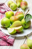 Healthy organic pears in white plate. Healthy organic pears in white plate on wooden background Stock Photo