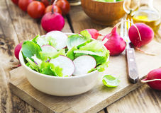 Healthy Organic Radish and Lettuce Spring Salad. Fresh Spring Vegetable Healthy Salad with Organic Lettuce and Radish, Basil Leaves on Wooden Background Royalty Free Stock Photos
