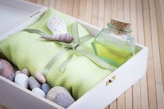 Healthy outfit for relaxation and SPA procedures with towel, stones and body oil royalty free stock photo