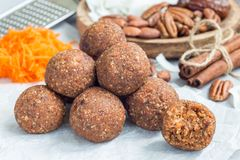 Healthy  paleo energy balls with carrot, nuts, dates and coconut flakes, on parchment, horizontal Royalty Free Stock Photos