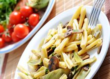 Healthy pasta. Homemade pasta with mushrooms and artichokes with vegetables on background Stock Photography