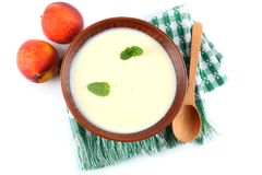 Healthy peach yogurt with peach gruit and mint leaves isolated on white background Stock Image