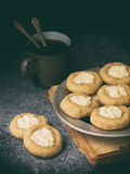 Healthy Peanut Butter Cheesecake Thumbprint Cookies. Delicious homemade shortbread and cup of tea on dark background. Copy space. Royalty Free Stock Photography