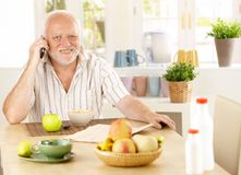 Healthy pensioner using cellphone at breakfast. Table, smiling at camera Royalty Free Stock Photo