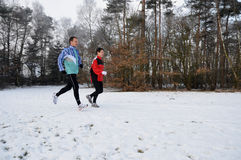 Healthy people running in the snow Royalty Free Stock Photos
