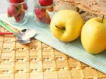 Healthy picnic. Apples and strawberries on wattled surface with checkered table cloth and bread in the background Royalty Free Stock Photos