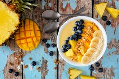 Pineapple, mango smoothie bowl with coconut, bananas, blueberries and granola, top view table scene on wood. Healthy pineapple, mango smoothie bowl with coconut stock images