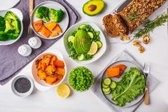 Healthy plant based food lunch, top view. Green salad, sweet potato, vegan cake, vegetables on white background. Healthy vegan food lunch, top view. Vegetarian stock photo