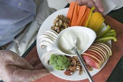 Healthy plate of food featuring yogurt, apple slices, walnuts and vegetables held by mans hands Royalty Free Stock Image