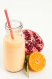 Healthy pomegranate smoothie. Healthy orange, pomegranate and kefir yogurt smoothie milkshake. Served with fresh sliced orange and whole pomegranate. Isolated on Royalty Free Stock Images
