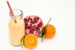 Healthy pomegranate smoothie. Healthy orange, pomegranate and kefir yogurt smoothie milkshake. Served with fresh sliced orange and whole pomegranate. Isolated on Stock Photos