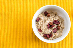 Healthy porridge breakfast. With hazelnuts and cranberries Stock Photos