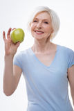 Healthy positive elderly lady posing with apple royalty free stock photo