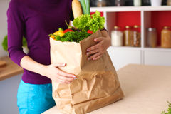 Healthy positive happy woman holding a paper shopping bag full of fruit and vegetables Royalty Free Stock Photo