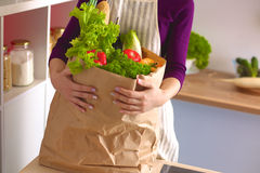 Healthy positive happy woman holding a paper shopping bag full of fruit and vegetables Royalty Free Stock Photos