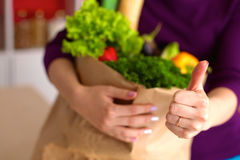 Healthy positive happy woman holding a paper shopping bag full of fruit and vegetables Stock Image