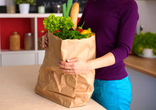 Healthy positive happy woman holding a paper shopping bag full of fruit and vegetables Stock Photos