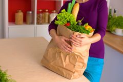 Healthy positive happy woman holding a paper shopping bag full of fruit and vegetables Stock Photo