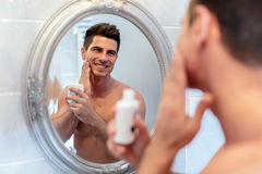 Healthy positive male treating sking with lotion Stock Photos