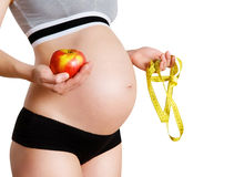 Healthy pregnancy. Close up of a pregnant woman holding apple and measure tape Stock Image
