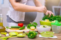 Healthy pregnancy concept. Happy pregnant woman cooking at home, doing fresh green salad, eating many different vegetables during pregnancy, healthy pregnancy stock photography