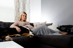 Healthy pregnant woman lying on a couch with her dog. Stock Image