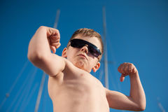 Healthy preschool child showing his biceps outdoors summer stock photo