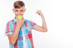 Healthy pretty boy is biting green fruit. Cheerful male teenager is eating an apple with joy. He is flexing his bicep and showing his strength. The schoolboy is Stock Image