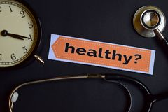 Healthy? on the print paper with Healthcare Concept Inspiration. alarm clock, Black stethoscope. stock images