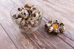Healthy quail eggs. Some quail eggs and yolk between its on the brown wooden table background Royalty Free Stock Photo